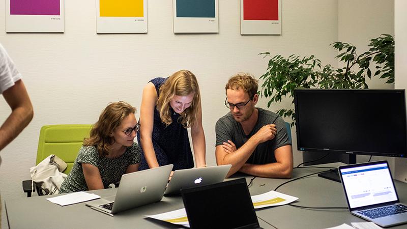 Menschen arbeiten zusammen am Laptop