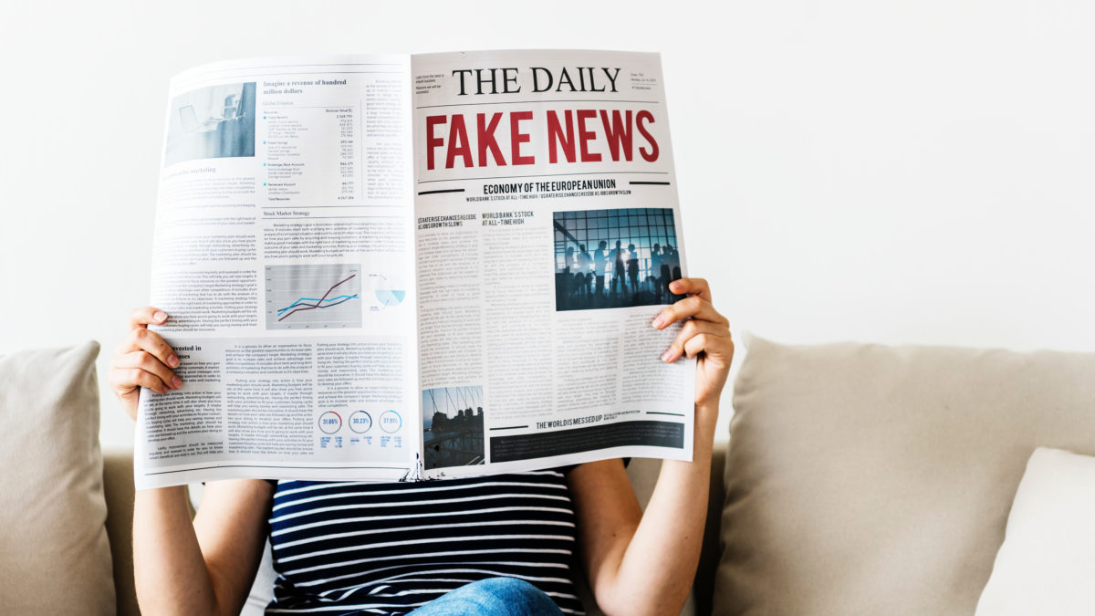 woman reading newspaper with fake news