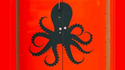 Ein schwarzer Octopus auf rotem Hintergrund.