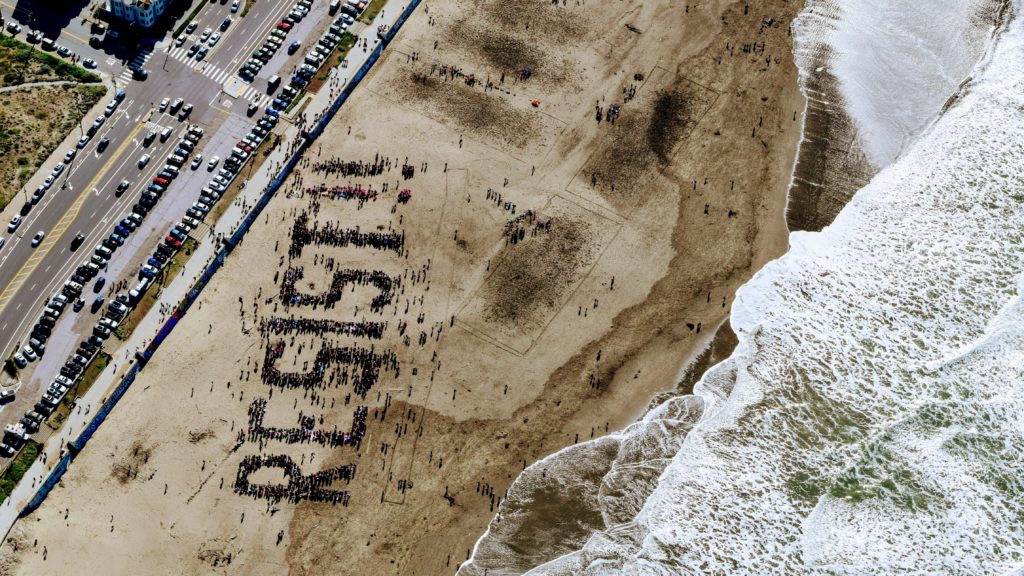 """Birds view of """"resist"""" written by people gathering on a beach"""