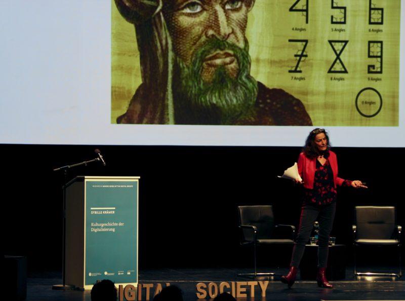 Auf dem Bild ist die Rednerin Sybille Krämer zu sehen, die vor dem Publikum spricht.