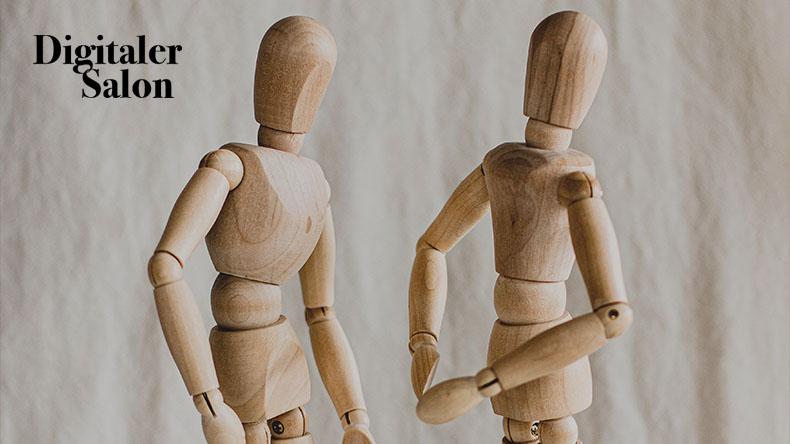 Zwei Holzfiguren diskutieren.