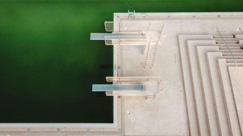 Das Bild zeigt einen Pool mit zwei Sprungbrettern, das Wasser ist grün.