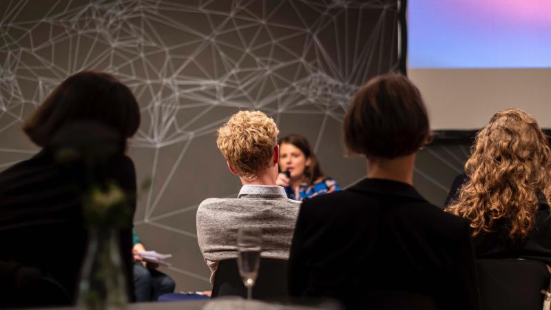 Titelbild für den Blogbeitrag. Zu sehen ist ein Publikum von hinten fotografiert. Sie hören einem Vortrag zu.