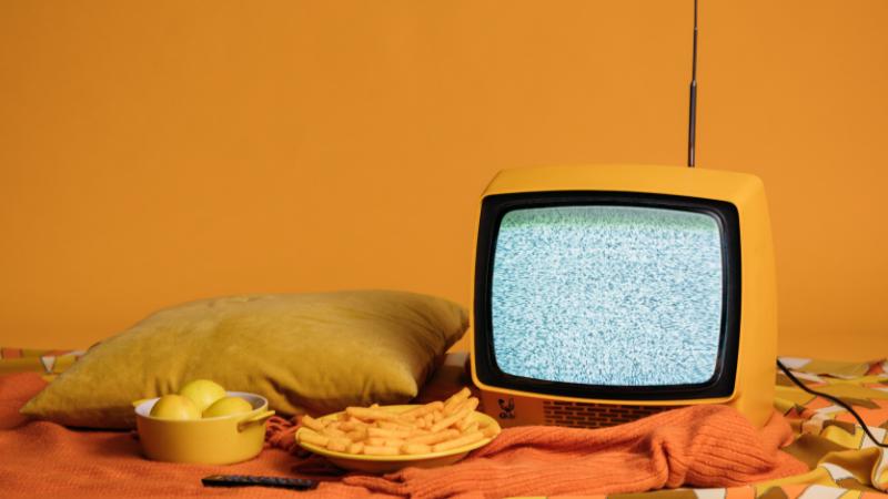 Titelbild für den Blogbeitrag. Ein Fernseher steht auf einer Orangen Decke neben