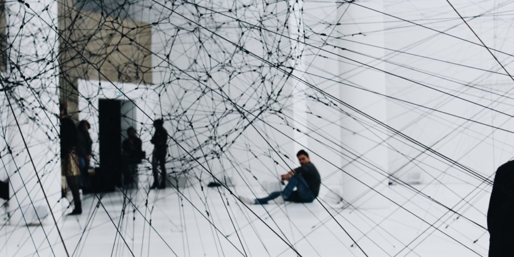 People standing behind a web of strings