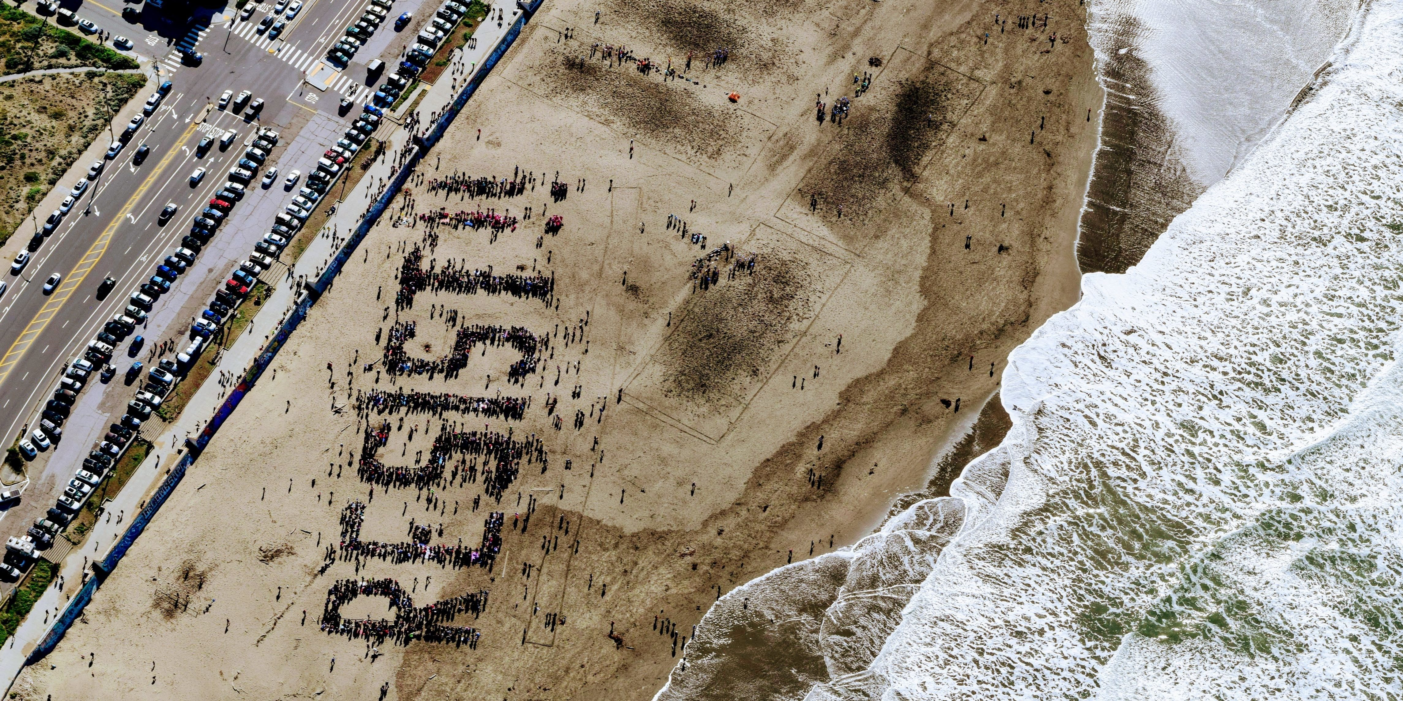 "Birds view of ""resist"" written by people gathering on a beach"